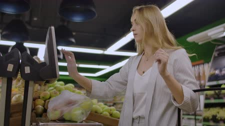 wegen : Young Woman Weighing Apples on the Electronic Scales. Housewife Shopping in a Supermarket in the Department of Fruit and Vegetables. Slow Motion. Sale, Shopping, Consumerism and People Concept.
