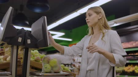 weighing machine : Middle-aged woman weighs a bag of apples in the supermarket.