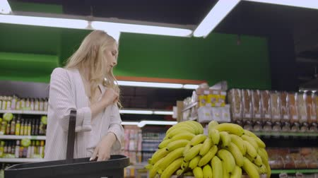 corredor : Young beautiful brunette girl in her 20s picking out bananas and putting them into shopping cart at the fruit and vegetable aisle in a grocery stor.
