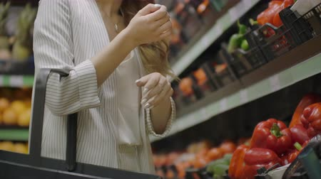 supermarket shelf : Hands take few colorful pepper one by one in marketplace and hold. Close up concept of selection, buy quality fruit or red vegetables. Young woman pick up some tasty freshness ingredient for cooking.