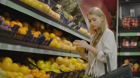 corredor : Woman hand choosing lemons at the grocery store picks up lemons at the fruit and vegetable aisle in a supermarket.