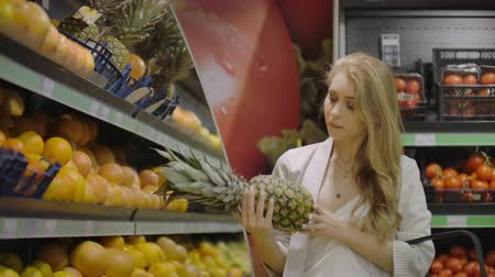 košíček : Woman choose one pineapple fruit and put it in shopping basket, take small pineapple lying near. Female customer at fruits and vegetables department of large modern supermarket. Dostupné videozáznamy