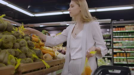 kool : At the Supermarket: Beautiful Young Woman Walks Through Fresh Produce Section, Chooses Vegetables and Puts them in Her Shopping Cart.