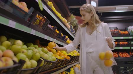 citrom és narancsfélék : A beautiful blonde in the supermarket chooses oranges and puts them in a bag to weigh on the scales