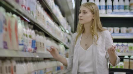 yoghurt : woman choosing and buying fresh organic dairy products at grocery store.