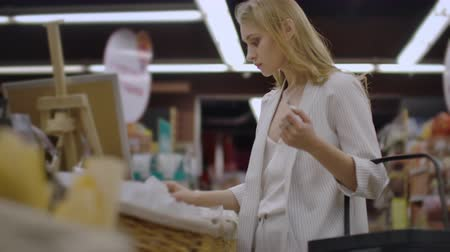 showcase : Attractive girl customer is buying bread in bakery department is shop, smelling it, smiling and putting in shopping trolley. Healthy lifestyle and supermarket concept