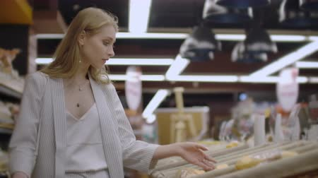 pastelaria : Attractive girl customer is buying bread in bakery department is shop, smelling it, smiling and putting in shopping trolley. Healthy lifestyle and supermarket concept