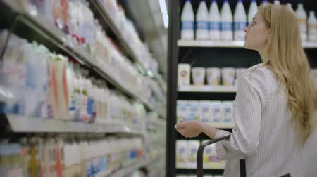twarożek : A woman walks along the refrigerator and chooses a bottle of milk, picks up and reads the label Wideo