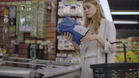 işlenmiş : Business woman in the supermarket takes out of the refrigerator frozen food reads the composition of the product and puts it in the basket Stok Video