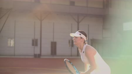 ütő : A professional woman in a white tight suit hits the ball with a racket and dynamically plays on the tennis court