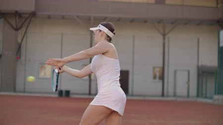 возвращение : Beautiful woman tennis player plays balls on the tennis court. Professional tennis player slow motion
