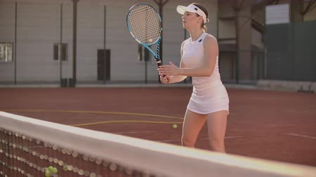 отскок : Woman tennis player on tennis court playing tennis in slow motion with racket and at sunset Стоковые видеозаписи