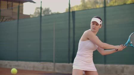 tennis stadium : Beautiful woman tennis player plays balls on the tennis court. Professional tennis player slow motion