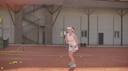 tennis stadium : Woman tennis player on tennis court playing tennis in slow motion with racket and at sunset Stock Footage
