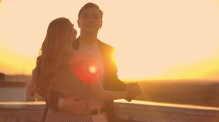 adore : Two lovers embracing dancing on top of a skyscraper overlooking the city at sunrise sunset. Romantic setting.