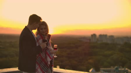 kırmızı şarap : Man and young pretty woman sitting on couch, holding wine glasses and kissing on rooftop terrace at sunset.