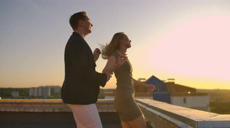 radiante : Cute lovers laughing running on the roof of the building at sunset on the background of the city and hugging standing at the edge. Romance and love.