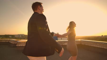 adore : Cute lovers laughing running on the roof of the building at sunset on the background of the city and hugging standing at the edge. Romance and love.