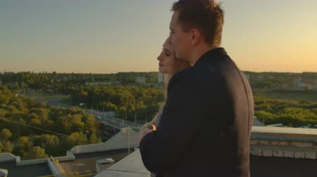 dekarz : Lovers man and woman, married couple, young come to the edge of the roof! And lovingly look at each other and hug Wideo