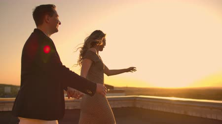 égalité : Young couple holding hands walking woman leading boyfriend the roof of the building at sunset POV travel concept. Carefree free lovers run on the roof laughing and smiling. Vidéos Libres De Droits
