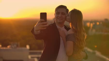adore : Standing on the roof at sunset a married couple a man and a woman hug and take a selfie on the phone. Take pictures of yourself standing on the roof and hug. Young people in love. Stock Footage
