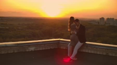 çok güzel : Lovely sweet happines couple sit on the roof top with amazing sunset view on the urban city town. They love each other hugs very tenderness sun goes between hair. Stok Video