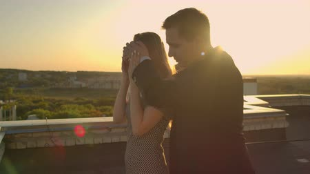 dekarz : A date on the roof, a man is leading girl closing hands eyes preparing romantic surprise. Show a beautiful view at sunset. The woman enjoys the surprise and smiles looking at the beautiful