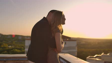 égalité hommes femmes : Young couple holding hands walking woman leading boyfriend the roof of the building at sunset POV travel concept. Carefree free lovers run on the roof laughing and smiling. Vidéos Libres De Droits