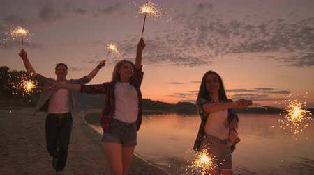 ırklararası : Cheerful male and female friends are running along the beach at sunset, holding sparkling fireworks and runaway lights in slow motion. Dancing and sunset party on the beach.