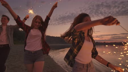 runaway : Cheerful male and female friends are running along the beach at sunset, holding sparkling fireworks and runaway lights in slow motion. Dancing and sunset party on the beach.
