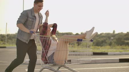 nákupní vozík : Slow motion: a Free and cheerful man and woman ride in carts in a supermarket Parking lot, shouting and raising their hands in the air.
