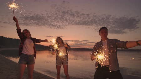 descida : Cheerful male and female friends are running along the beach at sunset, holding sparkling fireworks and runaway lights in slow motion. Dancing and sunset party on the beach.