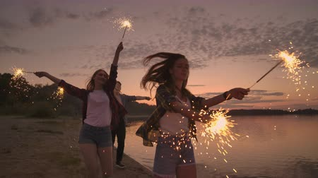 pirotecnia : Cheerful male and female friends are running along the beach at sunset, holding sparkling fireworks and runaway lights in slow motion. Dancing and sunset party on the beach.