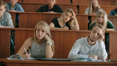 congress : In the Classroom Multi Ethnic Students Listening to a Lecturer and Writing in Notebooks. Smart Young People Study at the College