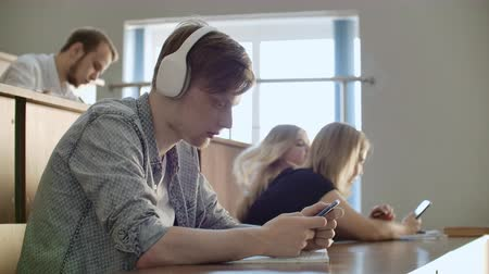 művelt : A student sitting in a university auditorium with a large group of people sits in headphones and listens to music and looks at the smartphone screen. It is in a state of calm. Class break.