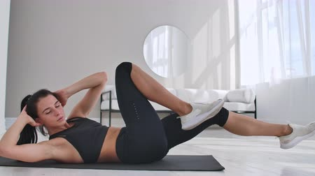 břišní : Young girl doing bicycle crunches exercise, working out at home. Young fitness girl doing easy intensive bicycle crunches exercise at home lying on floor, sporty.
