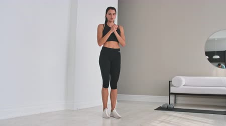 trabalhar fora : Beautiful Fit Girl Doing Home Workout Performing Lateral Lunges In A Sitting Room.