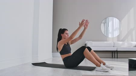 břišní : Home fitness concept. Woman doing abs crunches on floor at home, copy space.