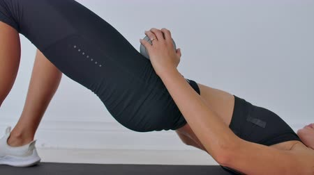pilates : Woman in sportswear doing hip bridge exercise. Joyful attractive young woman lying on floor in living room and doing hip bridge exercise. Stock Footage
