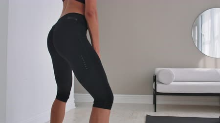 jimnastik : enduring strong determined beautiful concentrated tanned brunette wearing gray stylish sportive top and leggings woman doing deep squats with dumbbells in outstretched arms. Stok Video