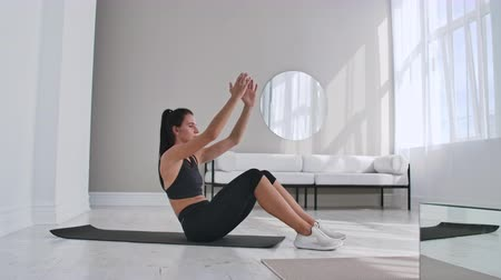 buikspieren : Home fitness concept. Woman doing abs crunches on floor at home, copy space.