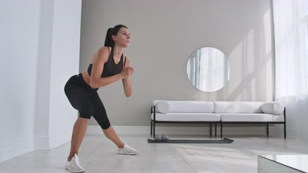 quadriceps : Cheerful sportive woman doing side lunges. Middle-aged happy sportswoman living room doing side lunges and smiling forward while training.