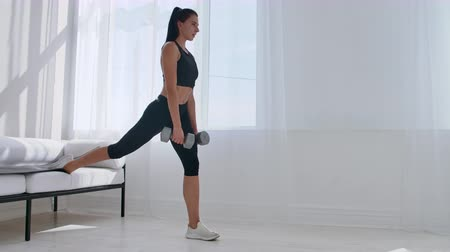 squats : Brunette in black sportswear in a white apartment makes a split squat with dumbbells in her hands leaning on the sofa with her foot Stock Footage
