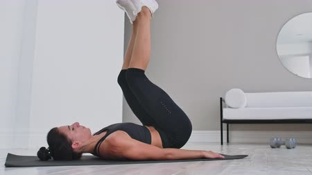 buikspieren : Strength training body weight workout woman athlete doing Flutter Kicks. European female adult doing floor exercises with Leg Raises to exercise abs muscles at home in his apartment.