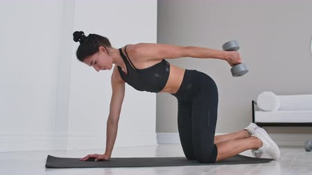 břišní : The girl in the white interior of the apartment to do exercises with dumbbells on the triceps. Extension dumbbell hand. Dostupné videozáznamy