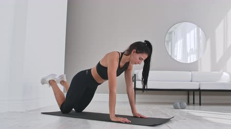 ajoelhado : Young sexy brunette woman in sportswear doing side plank exercise shifts hands while kneeling in white beautiful apartment interior. Vídeos