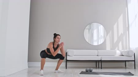 squats : Woman exercising jumping squats in home. Healthy female in sportswear doing jumping squats at home. Woman exercising at living room.