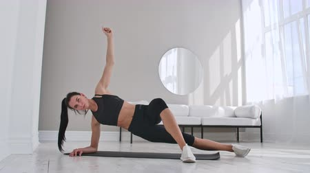 břišní : Young sexy brunette woman in sportswear doing side plank exercise with a tilt at home in a white interior. Slow motion. Dostupné videozáznamy