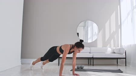 levegős : Beautiful slim woman in thirties with fair complexion does morning strenth and aerobic burpee exercises in modern airy room. Stock mozgókép