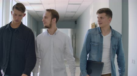 spolužák : Three male students walk down the corridor and talk